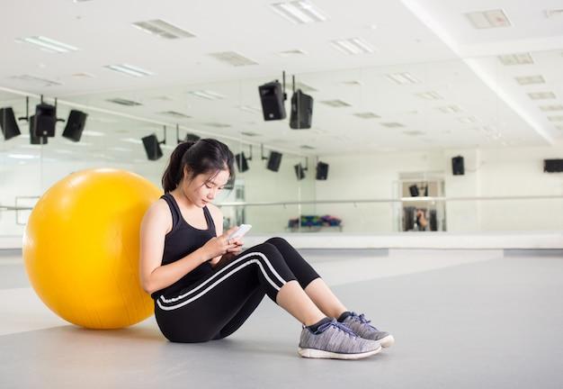 La hembra joven está jugando el teléfono móvil con la bola de la aptitud en gimnasio