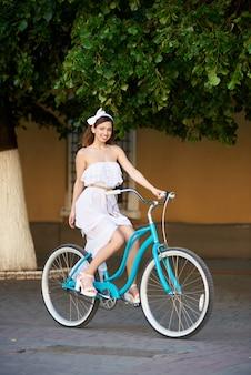Hembra joven montando en el asfalto en una bicicleta azul verano en la ciudad