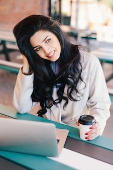Hembra joven con el pelo oscuro con café para llevar sentado delante del ordenador portátil abierto, navegar por internet.