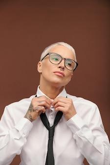 Hembra joven con pelo rubio teñido corto, piercing en la nariz y tatuajes haciendo botones en el cuello de la camisa blanca