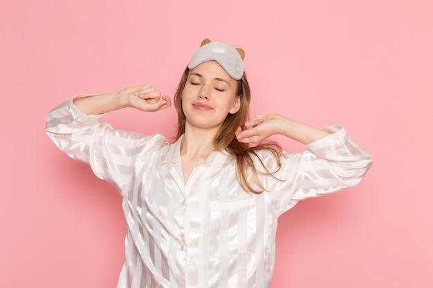Hembra joven en pijama y antifaz para dormir bostezando en rosa