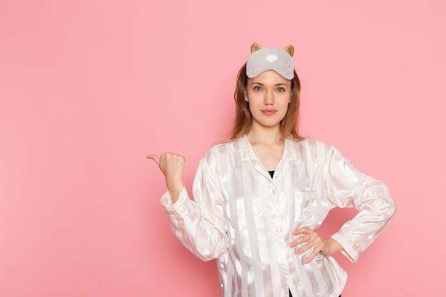 Hembra joven en pijama y antifaz para dormir posando con una sonrisa en rosa