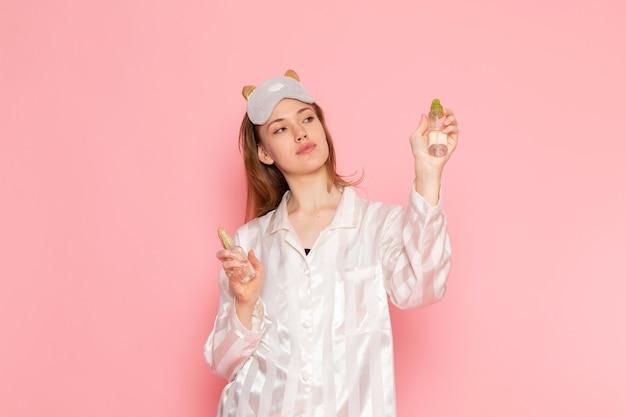 Hembra joven en pijama y antifaz para dormir posando sosteniendo spray en rosa