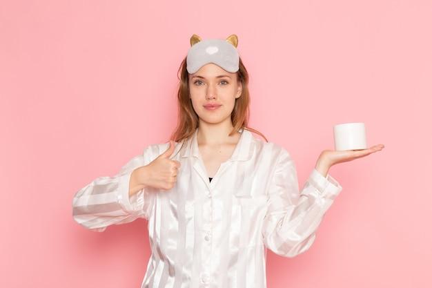 Hembra joven en pijama y antifaz para dormir sonriendo y sosteniendo crema en rosa