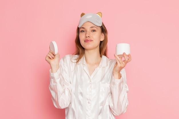 Hembra joven en pijama y antifaz para dormir sosteniendo crema y sonriendo en rosa