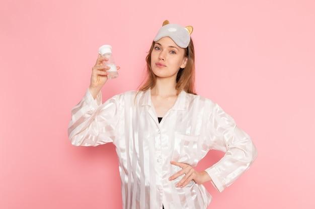 Hembra joven en pijama y antifaz para dormir sosteniendo spray de maquillaje y sonriendo en rosa