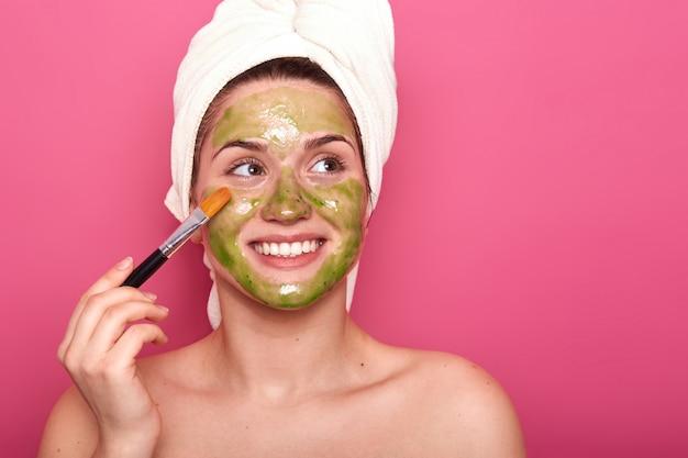 Hembra joven positiva alegre que pone la máscara colorida en su cara con la ayuda del cepillo profesional, mirando a un lado, siendo feliz. chica atractiva disfruta pasar tiempo haciendo procedimientos de belleza para la piel.