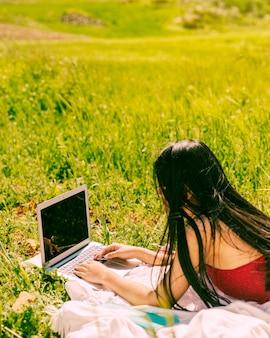 Hembra joven que practica surf en la computadora portátil en campo
