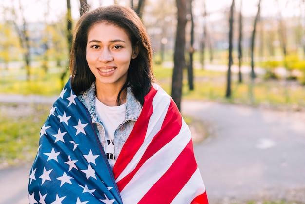 Hembra joven que sostiene la bandera americana en día soleado