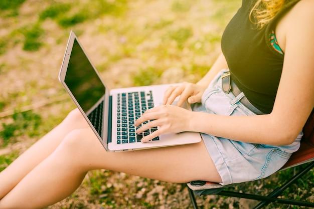 Hembra joven que trabaja en la computadora portátil en bosque