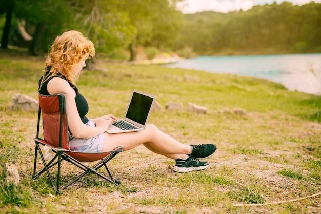 Hembra joven que usa la computadora portátil al aire libre