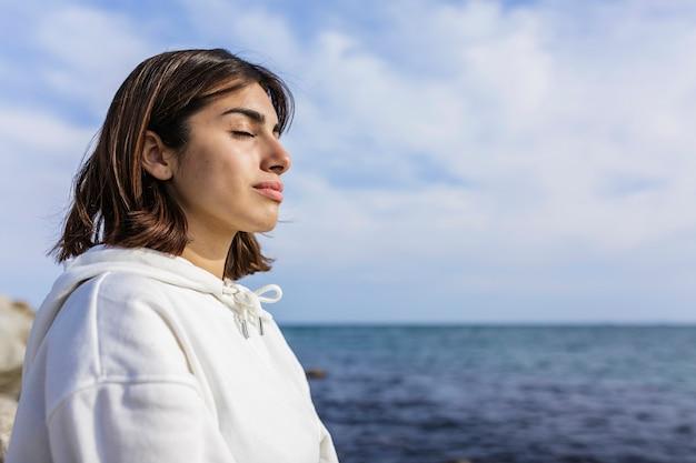 Hembra joven solitaria con los ojos cerrados descansando en la playa y disfrutando de la brisa fresca y la luz del sol