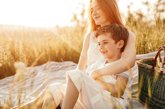 Hembra joven sonriendo y abrazando a niño alegre