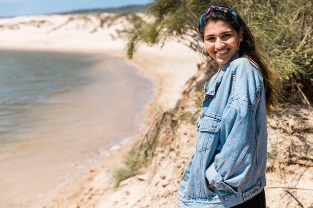 Hembra joven sonriente que se coloca en la costa