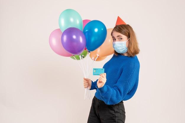 Hembra joven sosteniendo globos de colores en máscara con tarjeta bancaria en blanco