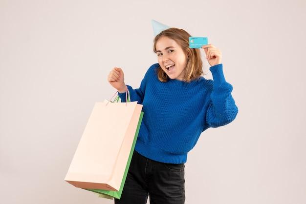 Hembra joven sosteniendo paquetes de compras y tarjeta bancaria en blanco