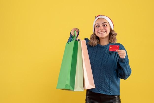 Hembra joven sosteniendo una tarjeta bancaria y paquetes después de comprar en amarillo