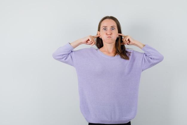 Hembra joven tapando los oídos con los dedos en blusa lila y mirando aburrido. vista frontal.