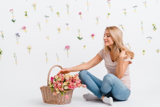 Hembra joven con tulipanes en canasta