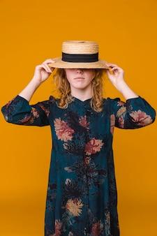 Hembra joven en vestido con sombrero beige