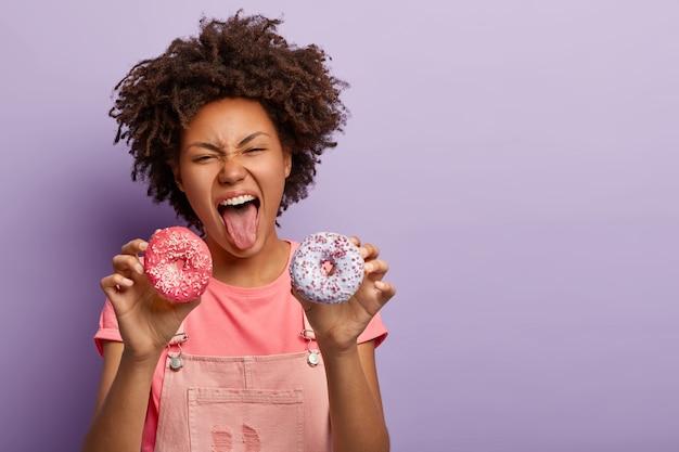 La hembra juguetona de piel oscura mantiene la boca abierta y muestra la lengua, tiene pasión por los deliciosos donuts glaseados, rompe la dieta y tiene una nutrición poco saludable, vestida de manera informal, disfruta de un delicioso refrigerio. dulce vida