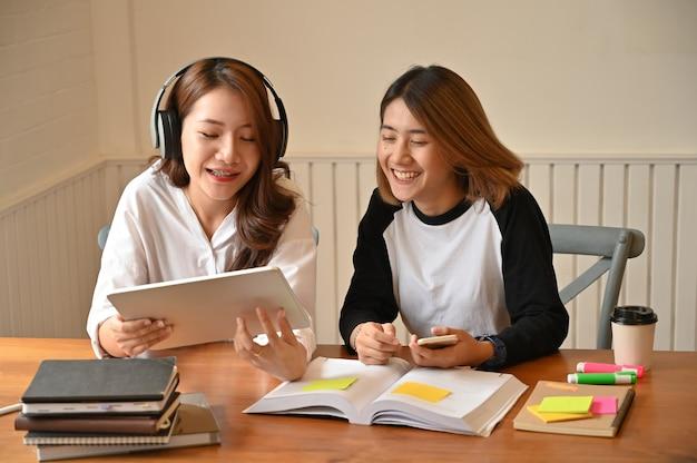 Hembra junto usando tableta hablando con educación.