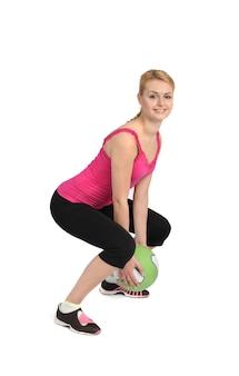 Hembra lanzando pelota medicinal ejercicio