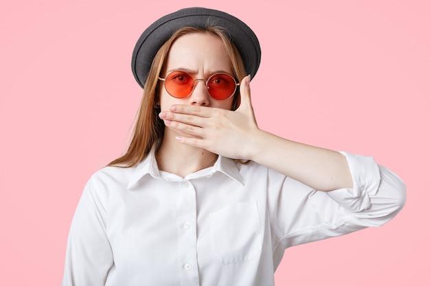 La hembra sin palabras y enojada cubre la boca mientras trata de guardar silencio, usa un elegante sombrero y elegantes sombras, aislado sobre la pared rosada del estudio encantadora mujer muda gesticula en interiores, muy molesta
