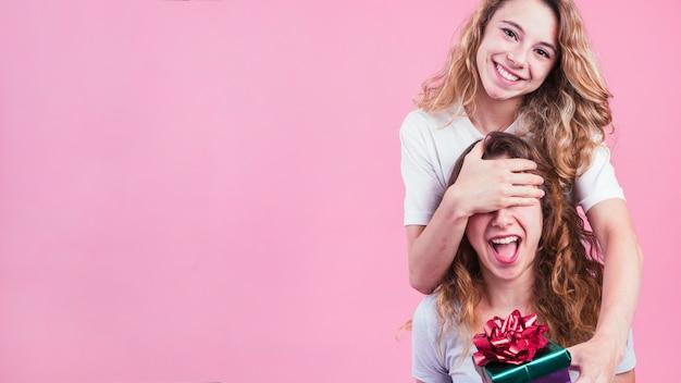 Hembra que cubre los ojos de su amigo que da la caja de regalo contra fondo rosado