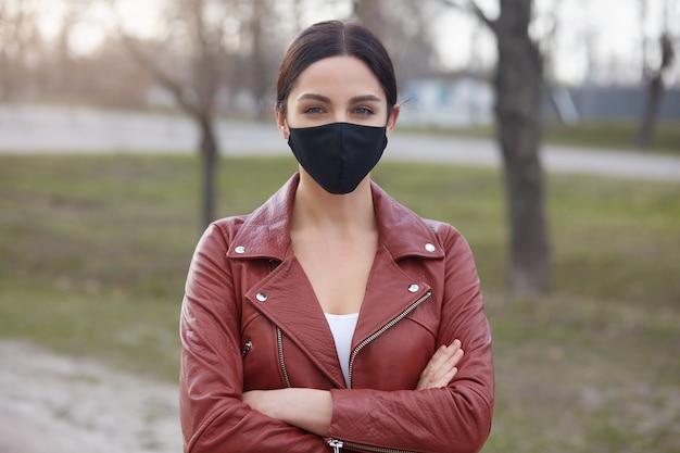 Hembra que respira aire fresco en lugares pobres, con elegante chaqueta de cuero y máscara antigripal