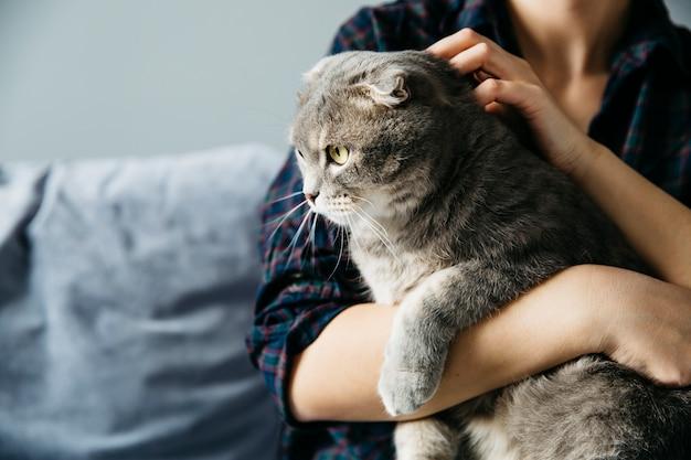 Hembra que se sostiene en manos gato