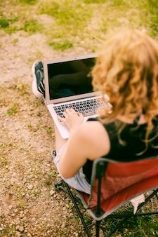 Hembra que trabaja en la computadora portátil en fondo de la naturaleza