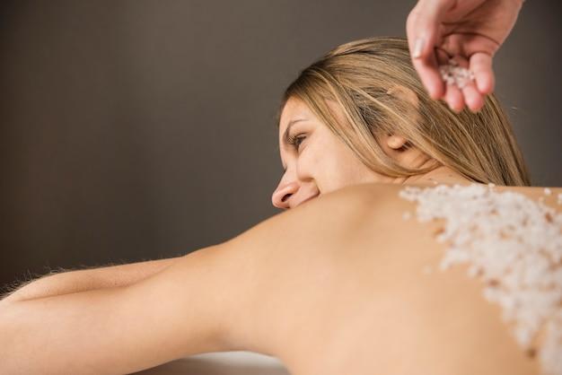Hembra recibiendo tratamiento de belleza de exfoliación con sal en el spa.