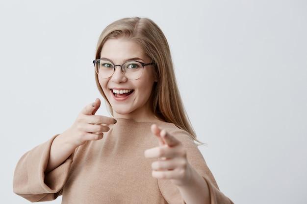 Hembra rubia con gafas que te indica con los dedos sonriendo ampliamente mientras tiene buen humor. alegre linda jovencita eligiendo a alguien, gesticulando con las manos aisladas