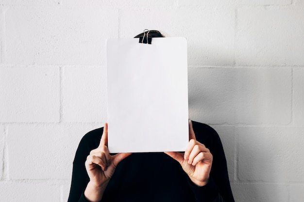 Una hembra sosteniendo un papel blanco frente a su cara contra una pared blanca