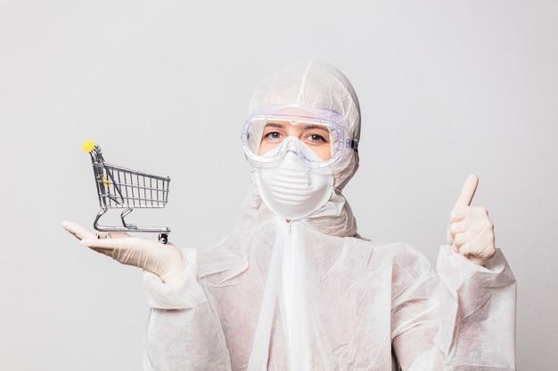 Hembra en traje de protección y gafas con máscara tiene carrito de compras