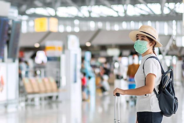 Las hembras jóvenes vistiendo mascarilla con equipaje caminando en la terminal del aeropuerto