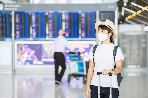 Las hembras jóvenes vistiendo mascarilla con equipaje comprobar el tiempo de vuelo en el aeropuerto