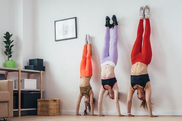 Las hembras que hacen el pino posan cerca de la pared. madre e hijas haciendo ejercicio en casa, deporte, familia.