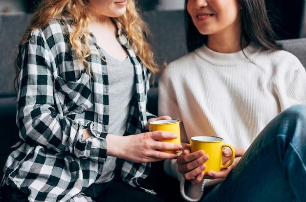 Hembras sonrientes sosteniendo tazas de café