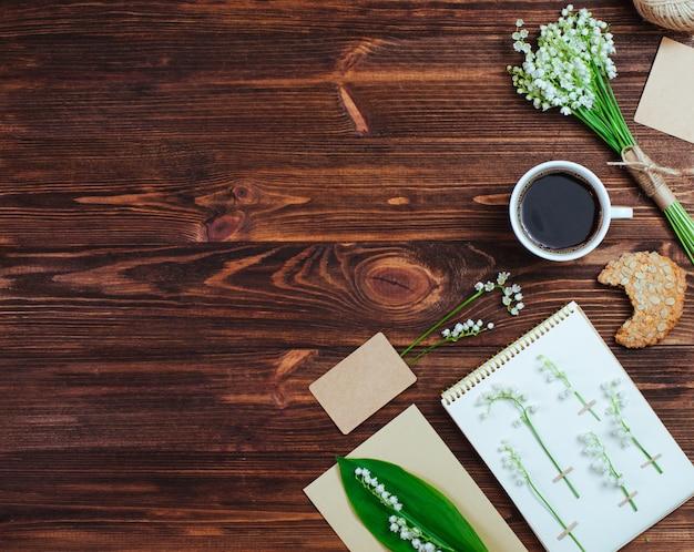 Herbario con lirios, bouquet, taza de café sobre fondo de madera rústico
