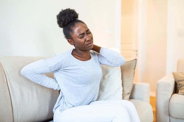 Herido joven afroamericana sentada en el sofá tocando la espalda sufre de dolor de espalda doloroso