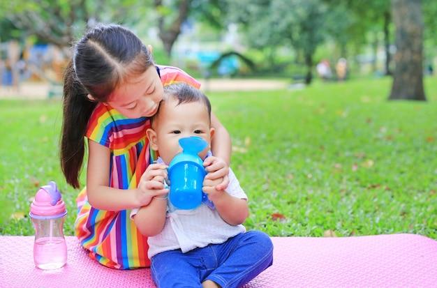 Hermana asiática cuida a su hermanito para beber agua de una taza para bebés con pajita