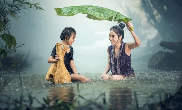 Hermana asiática bajo la lluvia, campo de tailandia