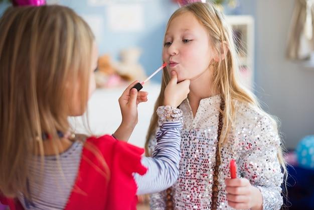 Una hermana ayudando a otra a maquillarse