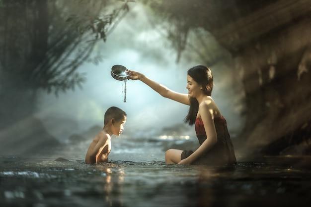Hermana y hermano bañándose en cascada, tailandia
