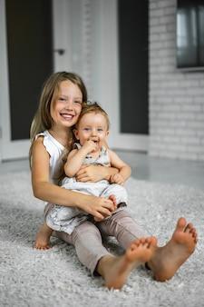 La hermana está jugando con su hermano menor. la hermana está sosteniendo a un hermanito. hermanos