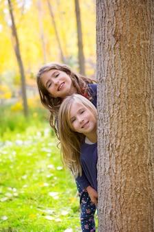 Hermana de otoño niñas de niños jugando en el tronco del bosque al aire libre
