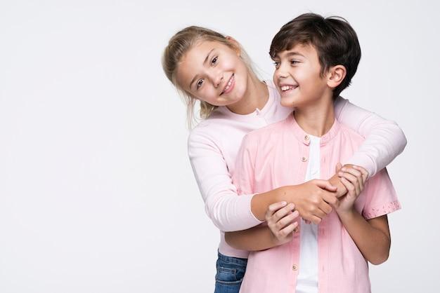Hermana sonriente abrazando a hermano con espacio de copia