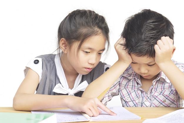La hermana trata de enseñarle a su travieso hermano menor a hacer la tarea.